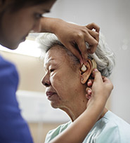 Elderly female patient getting a hearing aid fitted by a medical worker.
